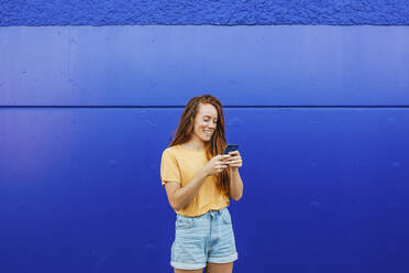 Smiling woman using mobile phone while standing against blue wall - MGRF00015