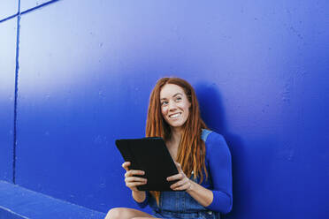 Smiling redhead woman using digital tablet while sitting against blue wall - MGRF00018