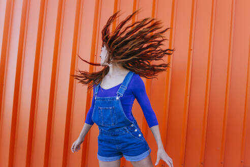 Playful woman tossing hair while standing against orange wall - MGRF00021
