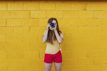 Young woman photographing through camera while standing against yellow wall - MGRF00027