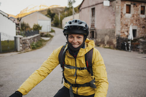 Smiling mid adult woman in warm clothing riding mountain bike on road while traveling to Somiedo Natural Park, Spain - DMGF00239