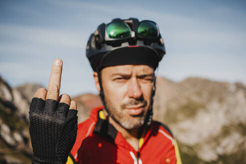Mid adult man showing middle finger while standing against mountain at Somiedo Natural Park, Spain - DMGF00248
