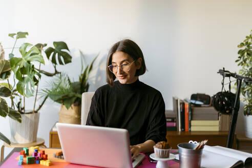 Female freelancer working on laptop sitting at home - VABF03798