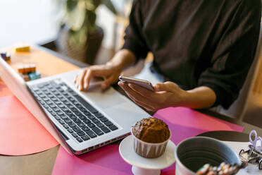 Businesswoman using laptop and smart phone while sitting at home - VABF03801