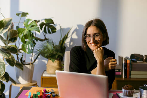 Smiling businesswoman with hand on chin using laptop while sitting at home - VABF03807