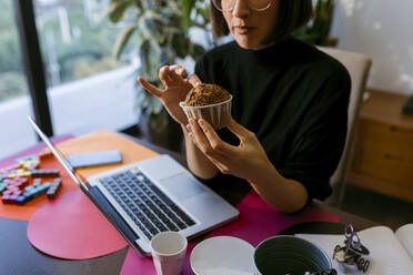 Female freelancer holding cake while sitting on chair at home - VABF03813