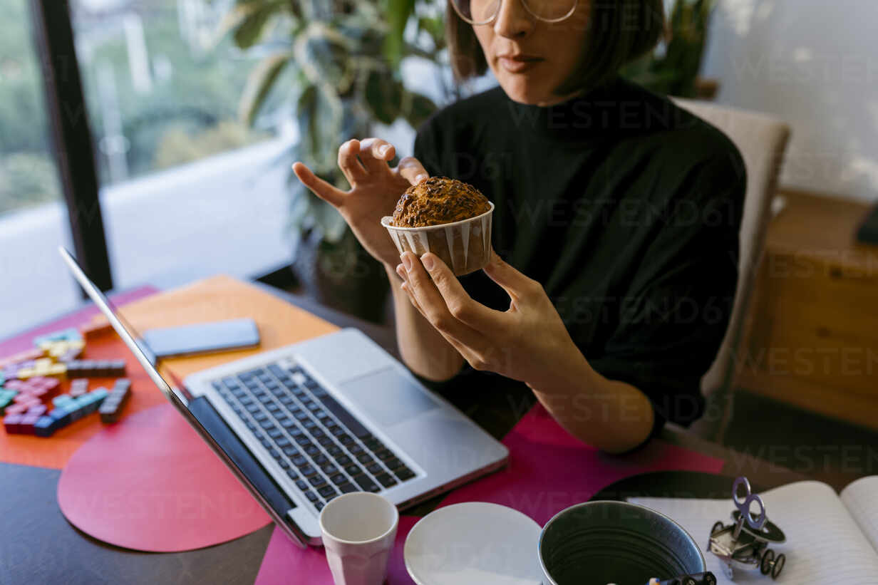 Female freelancer holding cake while sitting on chair at home - VABF03813 - Valentina Barreto/Westend61
