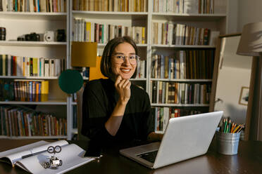 Businesswoman with hand on chin using laptop while sitting against bookshelf - VABF03819