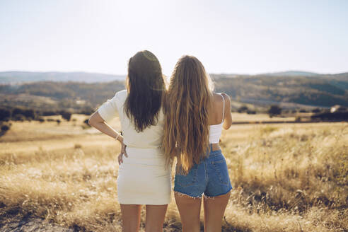 Female friends looking at view while standing on grassy field against sky during sunny day - RSGF00395