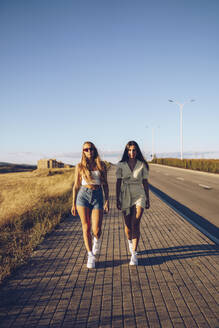 Young female friends walking on sidewalk against sky on sunny day - RSGF00404