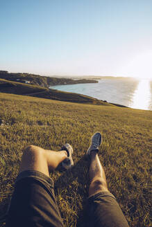 Man relaxing on hill against sky at Mirador de La Providencia, Gijon, Spain - RSGF00407