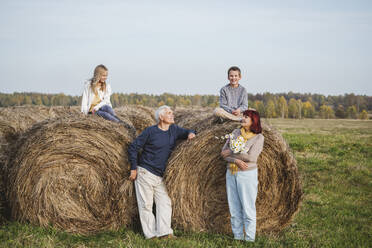 Senior couple with grandchildren sitting on hay bales on field during weekend - EYAF01393