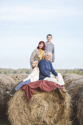 Boy and girl with grandchildren on hay bale against sky - EYAF01396