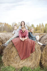 Happy parents resting with children on hay bale against sky during weekend - EYAF01417