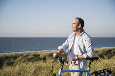 Cheerful mature man looking away while standing with bicycle at beach against clear sky - UUF21983