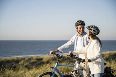 Happy couple in cycling helmets standing with bicycle at beach against clear sky - UUF21992