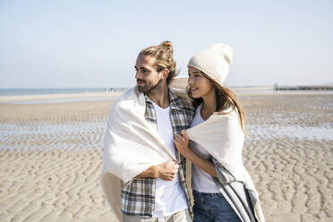 Thoughtful young couple covered in blanket looking away while standing at beach on sunny day - UUF22022