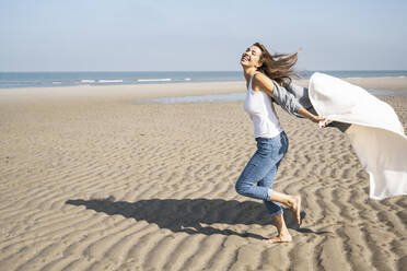 Carefree young woman running while holding blanket at beach during sunny day - UUF22031