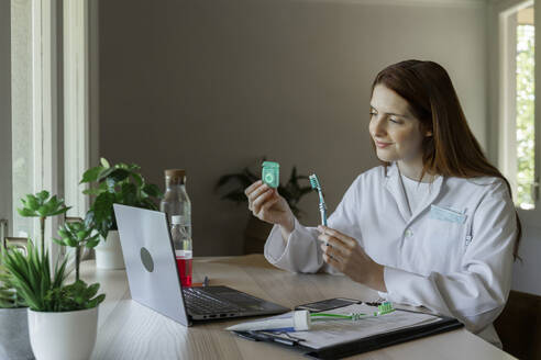 Smiling female dentist showing dental floss and toothbrush to patient through video call - AFVF07424