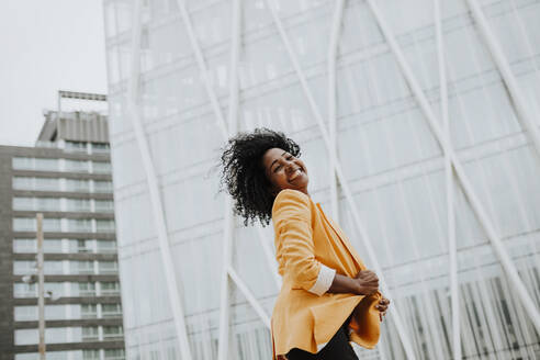 Smiling female entrepreneur with eyes closed standing against office building - GMLF00762