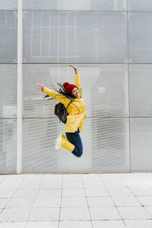 Happy woman jumping with arms raised on footpath against building exterior - EBBF01212