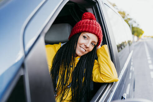 Woman with hand in hair looking out of car window during road trip - EBBF01239