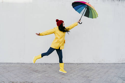 Woman with arms outstretched holding colorful umbrella while standing on footpath against wall - EBBF01269