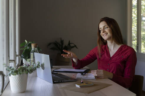 Smiling doctor talking on video call through laptop while sitting at home - AFVF07455