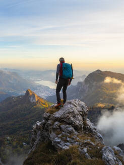 Pensive hiker with backpack standing on mountain peak during sunrise at Bergamasque Alps, Italy - MCVF00651