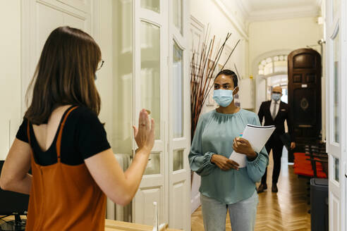 Female stopping businesswoman with protective face mask in corridor - JRFF04802