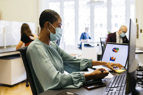 African businesswoman with safety mask working at office desk - JRFF04808