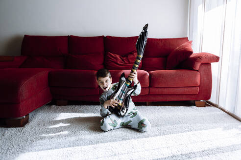 Happy boy playing guitar while kneeling against sofa in living room - XLGF00748