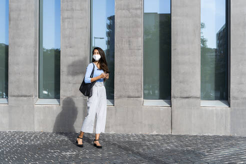 Businesswoman in face mask standing on footpath by building during coronavirus crisis - AFVF07461