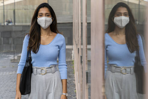 Young businesswoman in protective mask standing by glass window during pandemic - AFVF07467