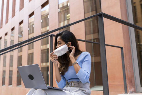 Young businesswoman wearing protective face mask while using laptop outside office building during pandemic - AFVF07488