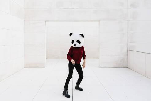 Woman wearing panda mask standing on tiled floor against doorway - XLGF00763