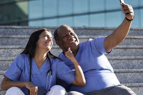 Smiling doctors taking selfie while sitting on staircase against hospital - GGGF00045