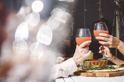 Female friends toasting drinks while sitting at restaurant - VYF00210