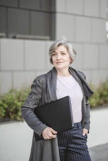 Businesswoman holding laptop while standing with hand in pocket against building - VYF00261