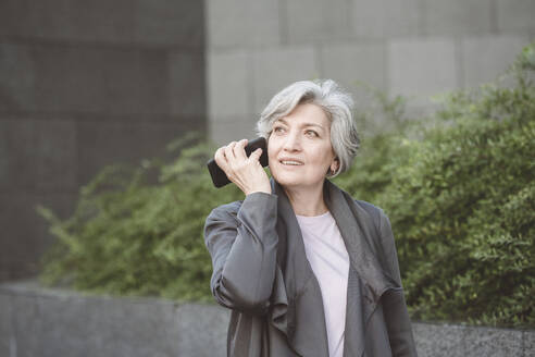 Smiling businesswoman talking on mobile phone while standing at city - VYF00270