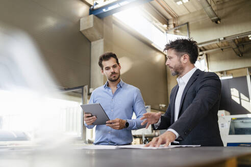 Businessman discussing with colleague holding digital tablet while standing at factory - DIGF12999