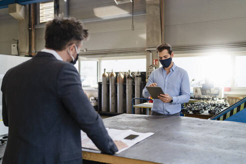 Young businessman with digital tablet and face mask working while standing with colleague at social distance in factory - DIGF13017