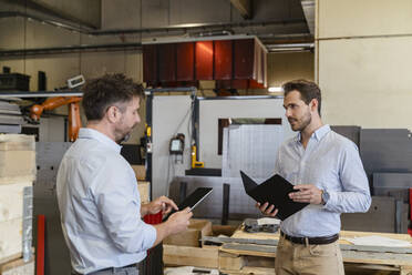 Business people with digital tablet and file having discussion while standing at factory - DIGF13074
