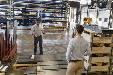 Business people standing by equipment while having discussion at factory - DIGF13077