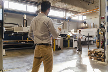 Businessman pointing toward equipment while talking with colleague at factory - DIGF13089