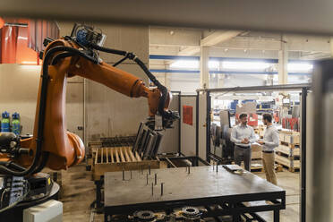 Business people having discussion while standing by automated robotic arm at factory - DIGF13092