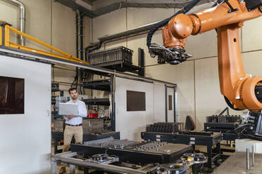 Businessman with laptop examining automatic robot arm machine at factory - DIGF13098