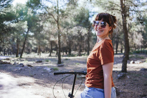 Smiling young woman in sunglasses with bicycle at countryside during weekend - MGRF00034