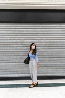 Contemplating woman with purse standing against shutter during COVID-19 - AFVF07541