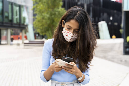 Woman wearing protective face mask while using smart phone in city during COVID-19 pandemic - AFVF07571